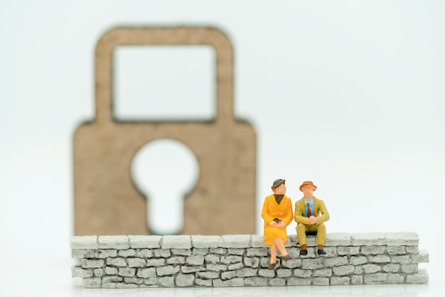 Miniature people: businessman sitting on wall with master key.