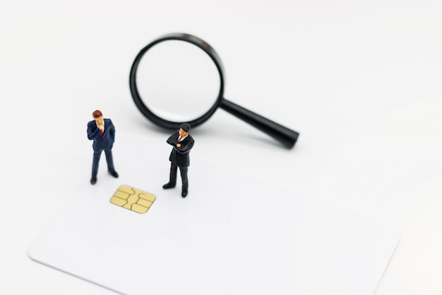 Miniature people: businessman stading with chip cards and magnifiers.