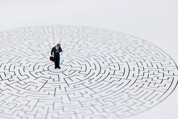 Miniature people: businessman standing on center of maze with look at watch.