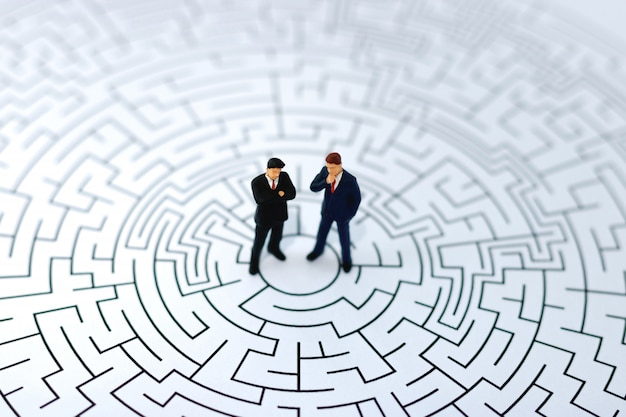 Miniature people: businessman standing on center of maze.
