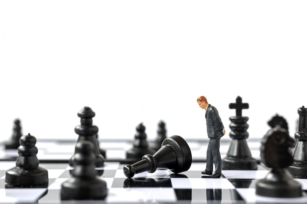 Miniature people businessman standing on chessboard
