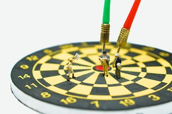 Miniature people, businessman standing on dartboard,red and green arrow hitting target center using