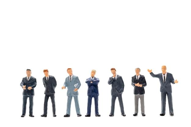 Миниатюрные люди, бизнесмен, стоя на белой стене
