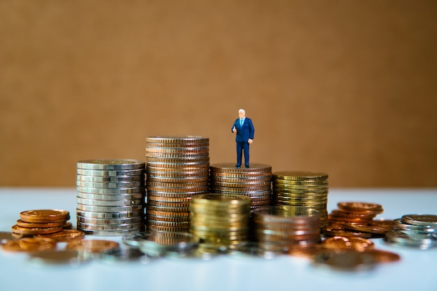 Miniature people, businessman standing on pile of coins