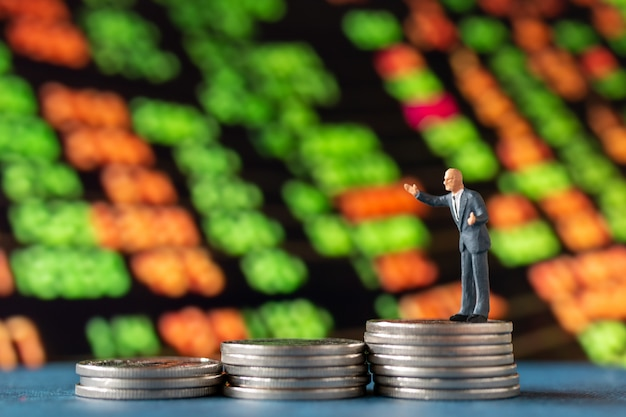 Miniature people , businessman standing on stack of  coins with graph display