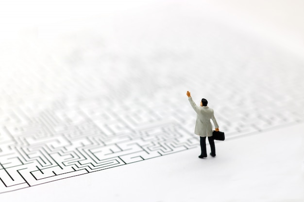 Miniature people: businessman standing on start of maze.