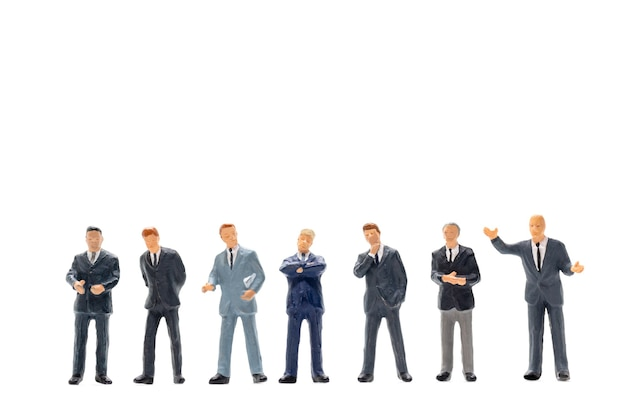 Miniature people, businessman standing on white wall