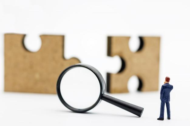 ミニチュアの人々:虫眼鏡とジグソーパズルで立っているビジネスマン。検索の概念: