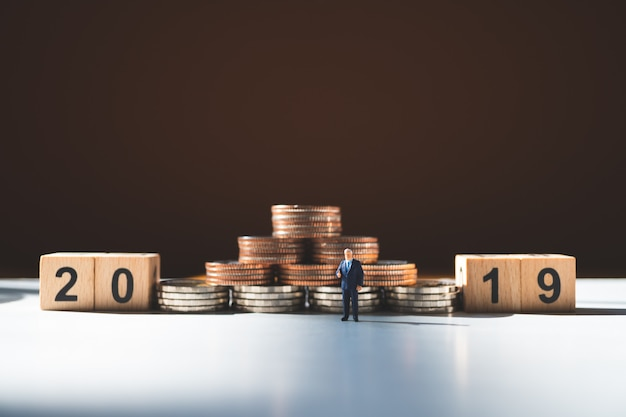 Miniature people, businessman standing with stack coins and year 2019