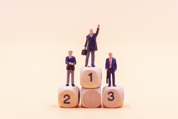 Miniature people businessman standing on wooden podium