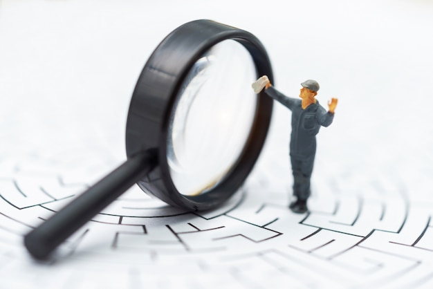 Miniature people: businessman use magnifying glass to find the route on the maze.