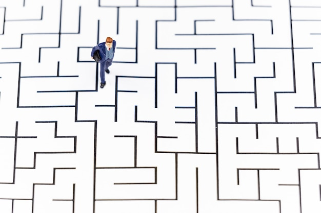 Miniature people businessman walking into a maze.