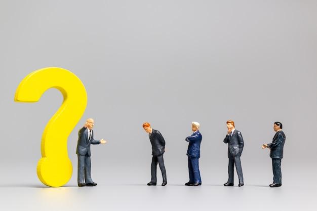 Миниатюрные люди, бизнесмен с большим вопросом. работники пытаются решить проблему концепции