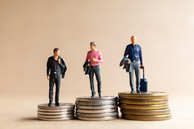 Миниатюрный бизнесмен людей с монетками. концепция роста бизнеса