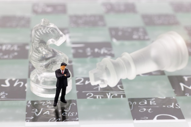 Miniature people, businessman with glass chess standing on chessboard.