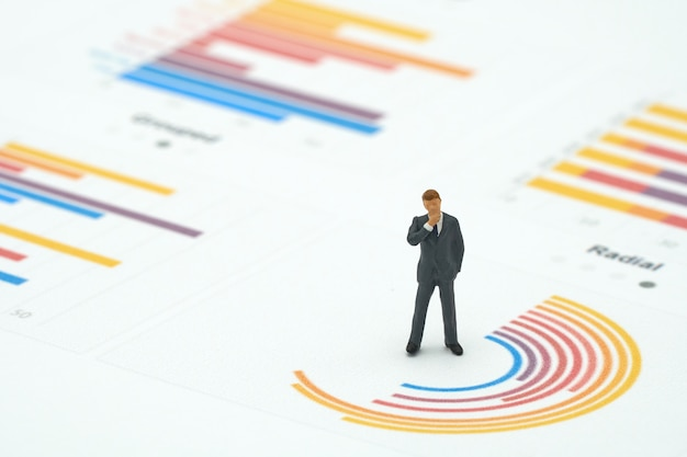 Miniature people businessmen analyze standing on circle graph
