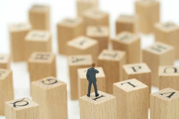 Miniature people businessmen analyze standing on wood words