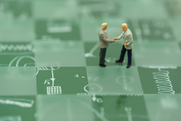 Miniature people businessmen handshake with green background.