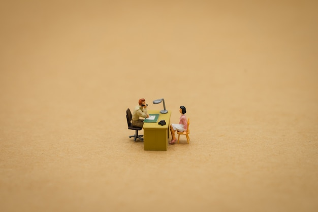 Miniature people businessmen interview candidates to consider working
