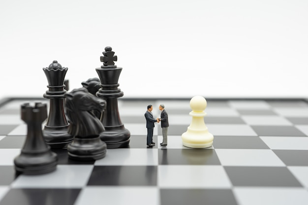 Miniature people businessmen shake hands standing on a chessboard with a chess