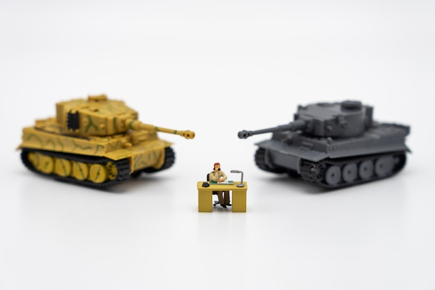 Miniature people businessmen sitting on a chessboard with a tank model