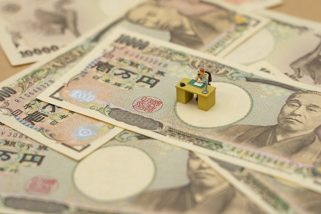 Miniature people businessmen sitting  with japanese banknotes worth 10,000 yen