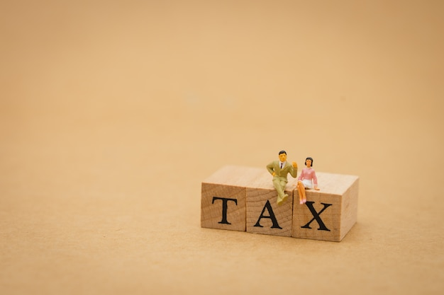 Miniature people businessmen sitting with wood word tax using as background