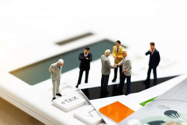 Miniature people: businessmen standing on calculator with hand handshake.