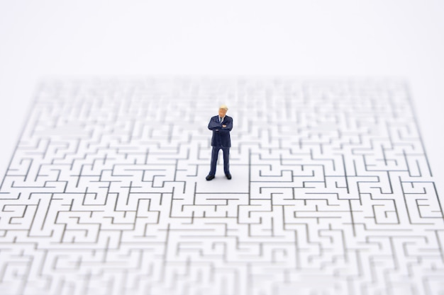 Miniature people businessmen standing in the center of the maze. business idea
