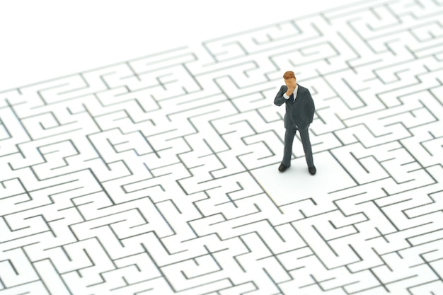 Miniature people businessmen standing in the center of the maze.
