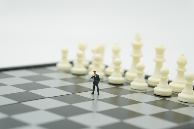 Miniature people businessmen standing chess analysis about business strategy.