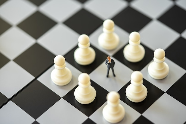 Miniature people businessmen standing chess analysis communicate