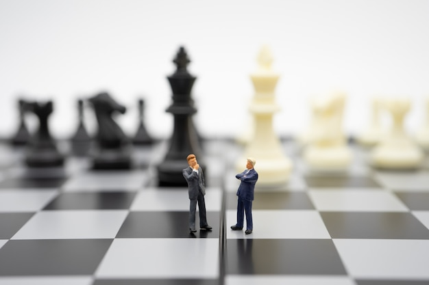 Miniature people businessmen standing on a chessboard with a chess piece on
