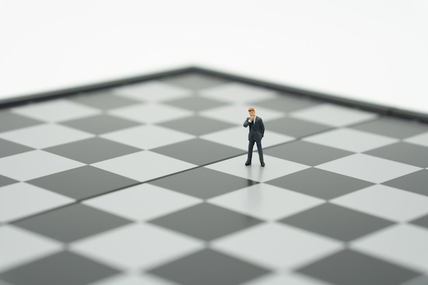 Miniature people businessmen standing on a chessboard with a chess piece