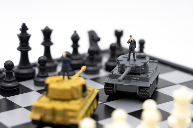 Miniature people businessmen standing on a chessboard with a tank model