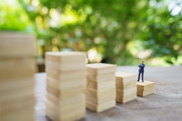 投資分析または投資に立つミニチュアの人々ビジネスマン。存在の概念