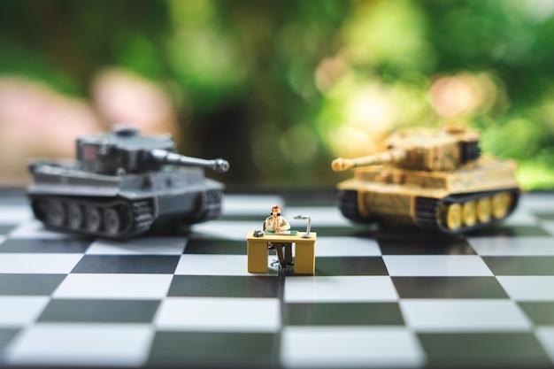 タンクモデルとチェス盤の上に立ってミニチュア人ビジネスマン