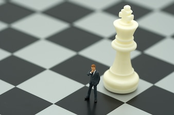 Miniature people businessmen standing on a chessboard