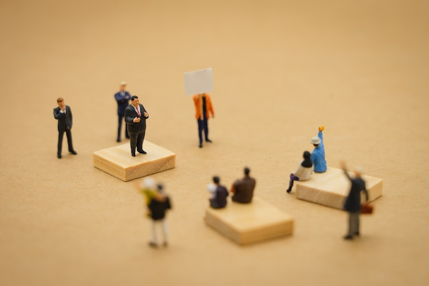 Miniature people businessmen standing policy statement to contend