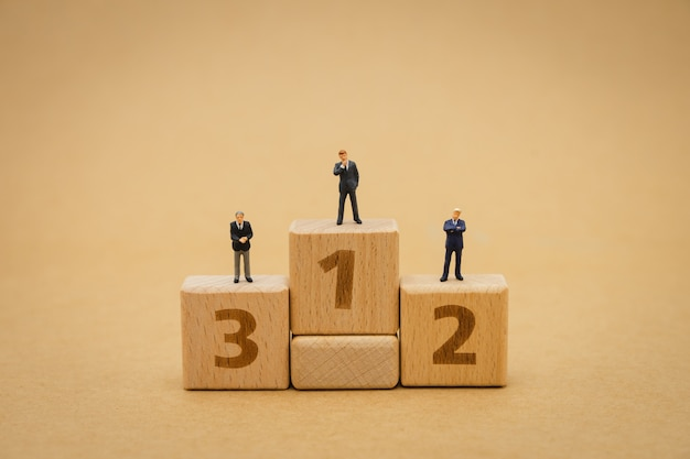 Miniature people businessmen standing on submitting on the podium award.