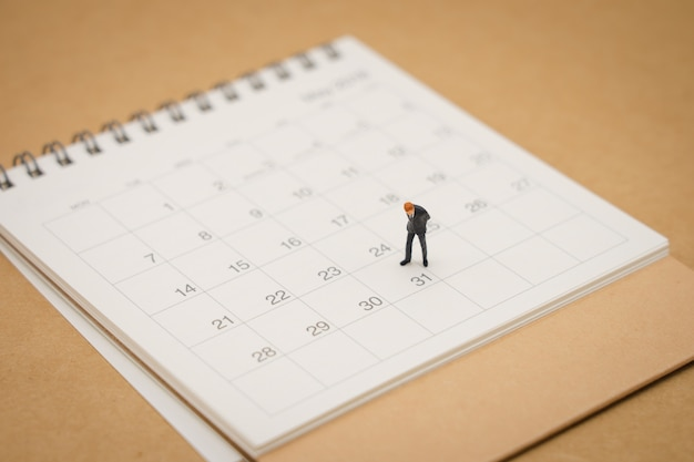 Miniature people businessmen standing on white calendar using as background