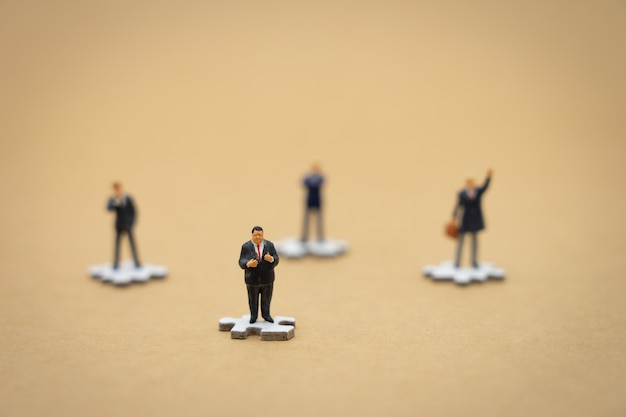 Miniature people businessmen standing on white jigsaw