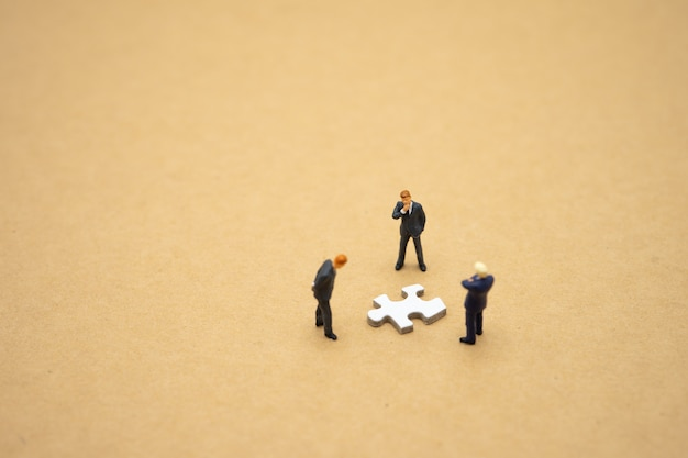 Miniature people businessmen standing on white jigsaw.