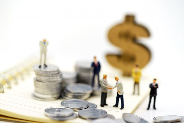 Miniature people,  businessmen standing with coins stack, finance and investment concept.