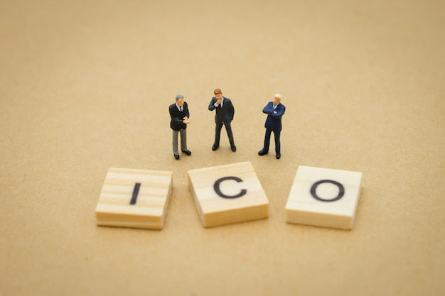 Miniature people businessmen standing with wood word ico (initial coin offering)