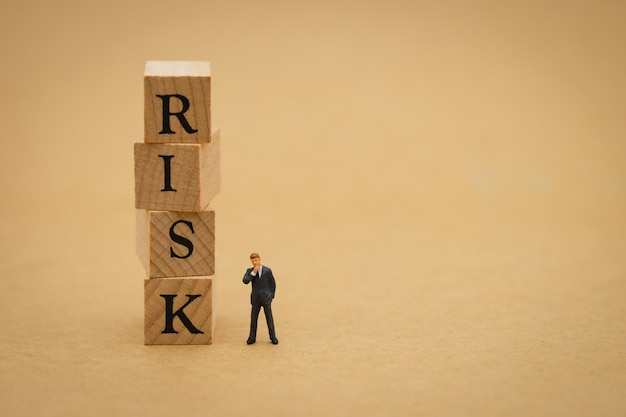 Miniature people businessmen standing with wood word risk