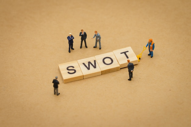 Miniature people businessmen standing with wood word swot using as background