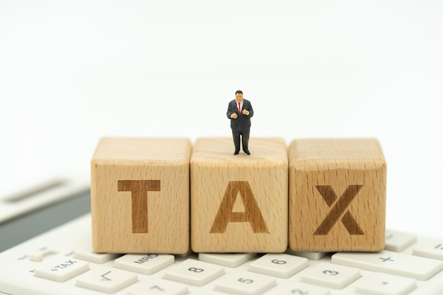 Miniature people businessmen standing with wood word tax using as background