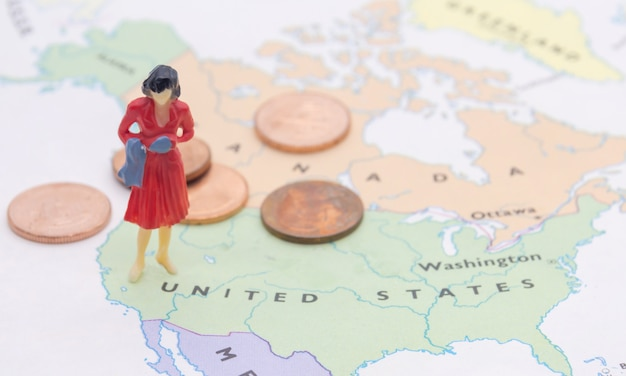 Miniature people, businesswoman standing on map american