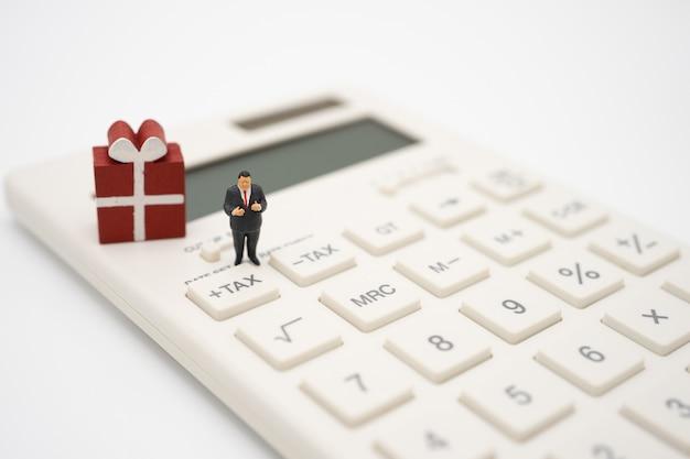 Miniature people on calculator.